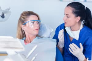 dentist discusses with female patient